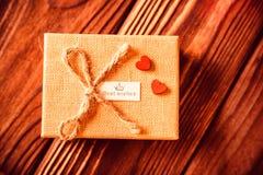El giftbox del ` s de la tarjeta del día de San Valentín andred corazones en la madera Fotografía de archivo