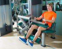 El gimnasio asentó al hombre rubio del ejercicio de la máquina del rizo de pierna Foto de archivo