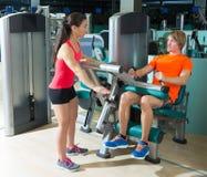 El gimnasio asentó al hombre rubio del ejercicio de la máquina del rizo de pierna Imagen de archivo
