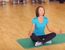 El gimnasio del deporte de los aeróbicos de la mujer ejercita en el piso, muchacha se sienta en la estera en actitud de la yoga Imagen de archivo