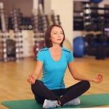 El gimnasio del deporte de los aeróbicos de la mujer ejercita en el piso, muchacha se sienta en la estera en actitud de la yoga Fotos de archivo libres de regalías