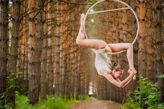 El gimnasta aéreo hermoso y agraciado hace ejercicios en el anillo Imágenes de archivo libres de regalías