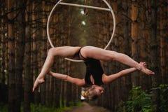 El gimnasta aéreo hermoso y agraciado hace ejercicios en el anillo Fotografía de archivo