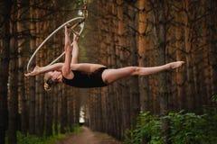 El gimnasta aéreo hermoso y agraciado hace ejercicios en el anillo en el bosque Imagen de archivo