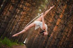 El gimnasta aéreo hermoso y agraciado realiza ejercicios en el anillo del aire Fotos de archivo libres de regalías