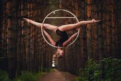 El gimnasta aéreo hermoso y agraciado realiza ejercicios en el anillo del aire Foto de archivo