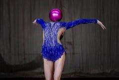 El gimnasta de la muchacha está haciendo frente adelante con la bola Imágenes de archivo libres de regalías