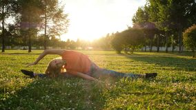 El gimnasta de la mujer se sienta en una secuencia en la hierba en un parque de la ciudad en naturaleza y hace estirando imagenes de archivo