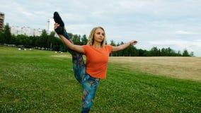 El gimnasta levanta una pierna en una guita vertical en un parque de la ciudad, movimiento de la cámara almacen de video