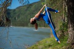 El gimnasta pelirrojo en un traje azul que hace los ejercicios difíciles en el aire suena en naturaleza Imagenes de archivo