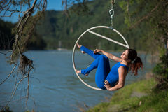 El gimnasta pelirrojo en un traje azul que hace los ejercicios difíciles en el aire suena en naturaleza Fotos de archivo libres de regalías