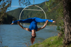 El gimnasta pelirrojo en un traje azul que hace los ejercicios difíciles en el aire suena en naturaleza Foto de archivo libre de regalías
