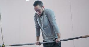 El gimnasta que hace tirón sube en barra en el gimnasio almacen de video