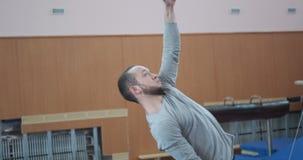 El gimnasta que hace una mano levanta en barra en el gimnasio metrajes
