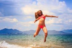 El gimnasta rubio en bikini salta sobre la cara del mar cerrada con el pelo Imagenes de archivo
