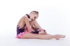 El gimnasta se sienta en el piso Fotografía de archivo