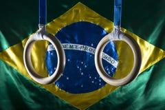 El gimnasta suena la ejecución con la bandera brasileña Fotografía de archivo libre de regalías