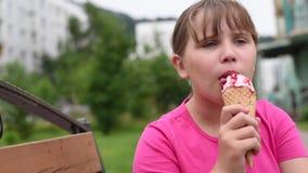 El girlie goza de un helado delicioso en un día caliente almacen de metraje de vídeo