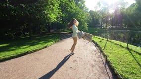 El giro de la mujer joven alrededor en parque del verano, disfruta de concepto de la vida almacen de metraje de vídeo