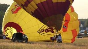 El globo amarillo del aire caliente se prepara para el vuelo en campo