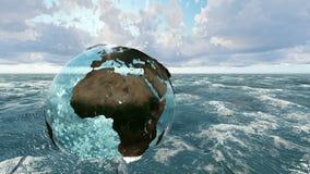 El globo con los océanos de cristal sobre el mar en el tiempo de la salida del sol ilustración del vector