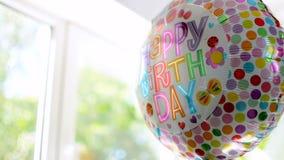 El globo de la celebración del feliz cumpleaños con reflexiones coloridas está girando lentamente almacen de video
