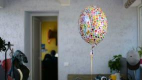 El globo de la celebración del feliz cumpleaños se fue después de texto reflector del partido y de girar metrajes