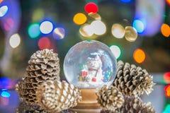 El globo de la nieve con el muñeco de nieve feliz en el árbol de navidad blured backgrou Fotos de archivo libres de regalías