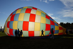 El globo del aire caliente siluetea Sun Foto de archivo