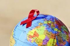 El globo del mundo con una cinta roja para la lucha contra AYUDA Imagen de archivo libre de regalías