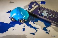 El globo del mundo y la bandera de la UE dentro de un smartphone y de una UE trazan, metáfora del sistema de Galileo imágenes de archivo libres de regalías