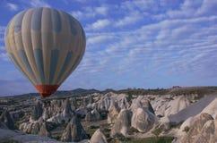 El globo vuela sobre las montañas Foto de archivo