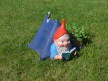El gnomo del jardín miente en su cabaña en un prado verde Imágenes de archivo libres de regalías