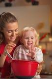 El goce feliz de la madre y del bebé hace las galletas de la Navidad Imágenes de archivo libres de regalías