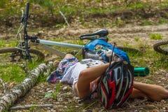 El goce hermoso del casco de la mujer que lleva joven relaja tiempo después de viaje de la bici en la opinión de la parte posteri Foto de archivo libre de regalías