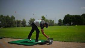 El golf del juego del hombre cerca del campo del golf almacen de metraje de vídeo