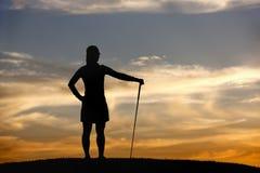El golfista en la puesta del sol mira la visión. Imagen de archivo