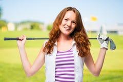 El golfista está sonriendo mientras que pone a un club de golf en sus hombros imagenes de archivo