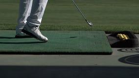 El golfista joven practica su oscilación del golf en el campo de prácticas, visión desde el lado metrajes