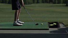 El golfista joven practica su oscilación del golf en el campo de prácticas, visión desde el lado almacen de metraje de vídeo