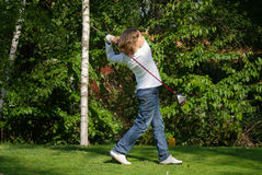 El golfista joven realiza un tiro de golf Fotos de archivo