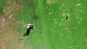 El golfista profesional golpea una bola blanca, jugando en un curso almacen de metraje de vídeo