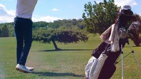 El golfista profesional golpea una bola con un club en un curso El golfista juega al golf, concepto de la forma de vida del depor metrajes