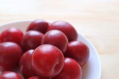El golfo maduro Ruby Plum Fruits Piled del color rojo para arriba en la placa blanca sirvió en la tabla de madera Fotos de archivo libres de regalías