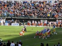 El golpeador de Illinois golpea fútbol del tiro de campo con el pie en como jum de los jugadores del UCLA Imagen de archivo libre de regalías