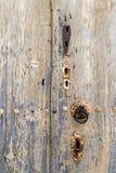 El golpeador y las cerraduras oxidados en una puerta de madera muy vieja Imágenes de archivo libres de regalías