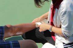 El golpear ligeramente en la pierna del jugador de tenis imagen de archivo