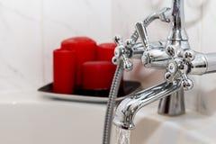 El golpecito/el grifo del cuarto de baño del vintage con las velas rojas se cierra para arriba Fotos de archivo libres de regalías