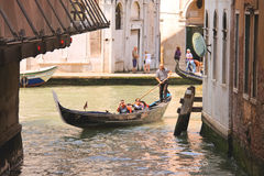 El gondolero navega con los turistas que se sientan en una góndola, Venecia, Ital Foto de archivo