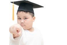 El graduado asiático del niño de la escuela con el casquillo de la graduación señaló el finger Foto de archivo